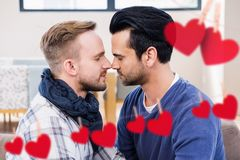 Composite image of red hanging heart and homosexual couple kissing. At home stock images