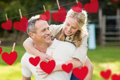 Composite image of red hanging heart and man giving a piggyback to woman. Composite image of red hanging heart and smiling man giving a piggyback to woman royalty free stock image