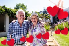 Composite image of red hanging heart and senior couple standing with arm around in park. Composite image of red hanging heart and happy senior couple standing royalty free stock image