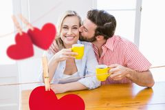 Composite image of red hanging hearts and couple kissing while having coffee Stock Photos