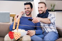 Composite image of red hanging hearts and friends watching tv in living room Stock Image