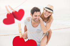 Composite image of red hanging hearts and man giving piggyback to woman Royalty Free Stock Photo