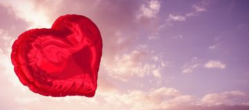 Composite image of red heart balloon. Red heart balloon against cloudy sky landscape Stock Images