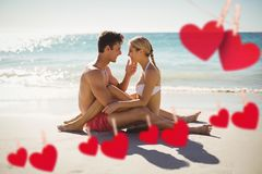 Composite image of red hearts and couple cuddling on beach Royalty Free Stock Photos