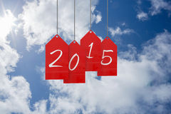 Composite image of 2015 red tags. 2015 red tags against bright blue sky with clouds Royalty Free Stock Image
