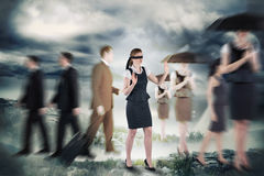 Composite image of redhead businesswoman in a blindfold Stock Photo