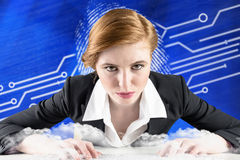 Composite image of redhead businesswoman sitting at desk typing Stock Image