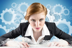 Composite image of redhead businesswoman sitting at desk typing Royalty Free Stock Photography