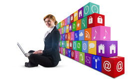 Composite image of redhead businesswoman using her laptop Royalty Free Stock Photos