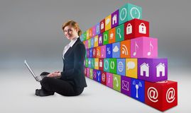 Composite image of redhead businesswoman using her laptop Stock Images