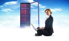 Composite image of redhead businesswoman using her laptop Royalty Free Stock Photo