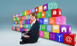 Composite image of redhead businesswoman using her tablet pc Stock Photography