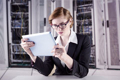 Composite image of redhead businesswoman using her tablet pc Stock Photo