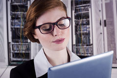 Composite image of redhead businesswoman using her tablet pc Stock Photos