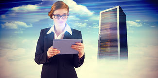 Composite image of redhead businesswoman using her tablet pc Royalty Free Stock Images