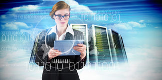 Composite image of redhead businesswoman using her tablet pc Royalty Free Stock Photos