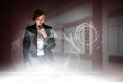 Composite image of redhead businesswoman using interactive desk Stock Photography