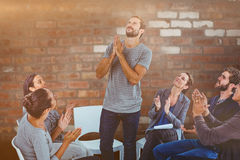 Composite image of rehab group applauding delighted man standing up Stock Image