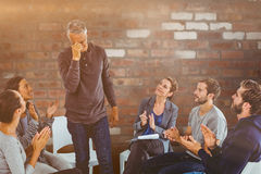Composite image of rehab group applauding delighted man standing up Royalty Free Stock Photos