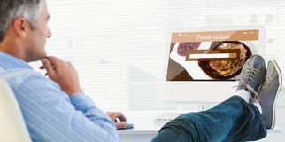 Composite image of relaxed man with feet on desk using computer Stock Images