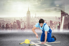 Composite image of repairman fixing screw on plank Royalty Free Stock Image