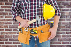 Composite image of repairman with hard hat and hammer Stock Photo