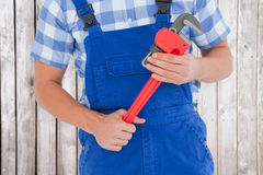 Composite image of repairman holding adjustable pliers Royalty Free Stock Photography