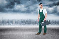 Composite image of repairman holding toolbox Royalty Free Stock Image