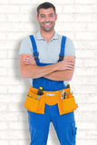 Composite image of repairman in overalls wearing tool belt standing arms crossed. Repairman in overalls wearing tool belt standing arms crossed against white Stock Photography