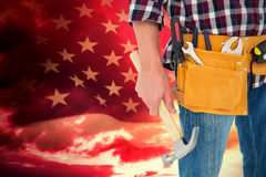 Composite image of repairman wearing tool belt while holding hammer. Repairman wearing tool belt while holding hammer against american flag rippling over grassy Royalty Free Stock Photos