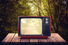 Composite image of retro tv. Retro tv against path in woods Royalty Free Stock Photo