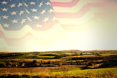 Composite image of rippled us flag. Rippled US flag against scenic landscape Stock Photography