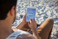 Composite image of roaming text on european union flag. Roaming text on European Union flag against high angle view of man using digital tablet at beach Royalty Free Stock Photography