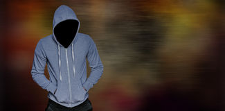 Composite image of robber in gray hoodie with hands in pockets. Robber in gray hoodie with hands in pockets against dark background Stock Images