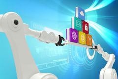 Composite image of robotic hands holding computer icons against blue background Royalty Free Stock Images