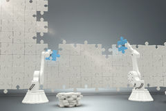 Composite image of robots arranging jigsaw pieces on puzzle 3d Royalty Free Stock Photos