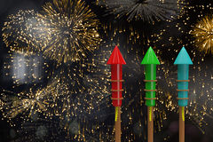 Composite image of rockets for fireworks. Rockets for fireworks against colourful fireworks exploding on black background Royalty Free Stock Images