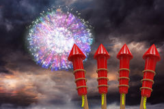 Composite image of rockets for fireworks. Rockets for fireworks against colourful fireworks exploding on black background Stock Photos