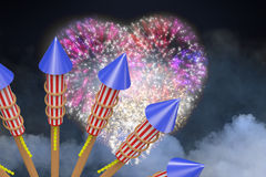 Composite image of rockets for fireworks. Rockets for fireworks against colourful fireworks exploding on black background Stock Photo