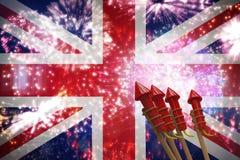 Composite image of rockets for fireworks. Rockets for fireworks against colourful fireworks exploding on black background Stock Images