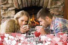 Composite image of romantic couple drinking tea in front of lit fireplace. Romantic couple drinking tea in front of lit fireplace against happy valentines day Royalty Free Stock Image