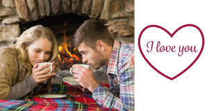 Composite image of romantic couple drinking tea in front of lit fireplace. Romantic couple drinking tea in front of lit fireplace against valentines love hearts Royalty Free Stock Image