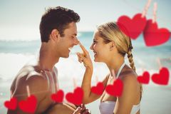 Composite image of romantic couple enjoying on the beach Royalty Free Stock Images