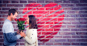 Composite image of romantic couple holding red roses Royalty Free Stock Image