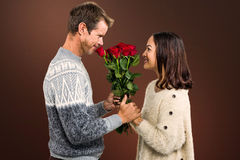 Composite image of romantic couple holding red roses Royalty Free Stock Images