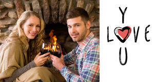 Composite image of romantic couple toasting wineglasses in front of lit fireplace. Romantic couple toasting wineglasses in front of lit fireplace against cute Royalty Free Stock Images