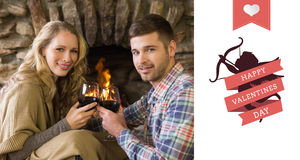 Composite image of romantic couple toasting wineglasses in front of lit fireplace. Romantic couple toasting wineglasses in front of lit fireplace against happy Royalty Free Stock Image