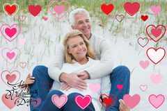 Composite image of romantic senior couple relaxing at beach. Romantic senior couple relaxing at beach against happy valentines day stock photos