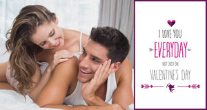 Composite image of romantic young couple in bed at home. Romantic young couple in bed at home against valentines day greeting stock photo