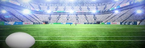 Composite image of rugby ball. Rugby ball against stadium against sky stock photos